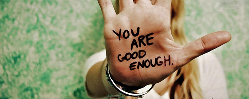 Hand with words you are good enough written on it