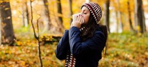 Lady blowing her nose from fall allergies